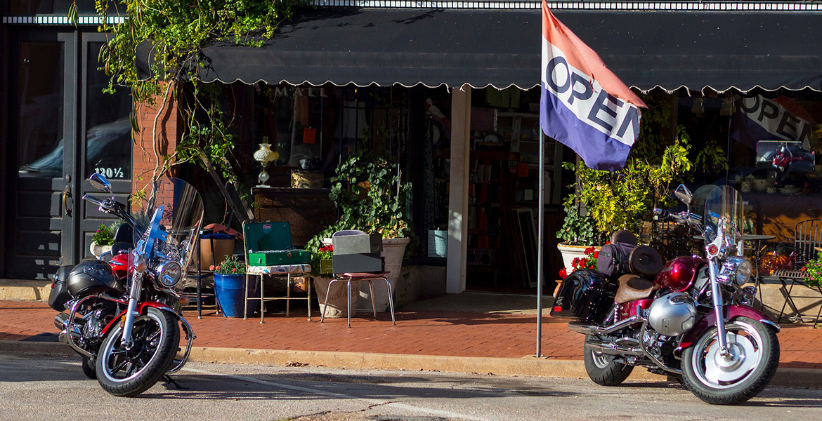Photo of main street business with big open flag out front.
