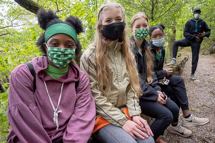 Photo of masked 4-H'ers (following pandemic guidelines) pausing for a rest along a woodlands trail.