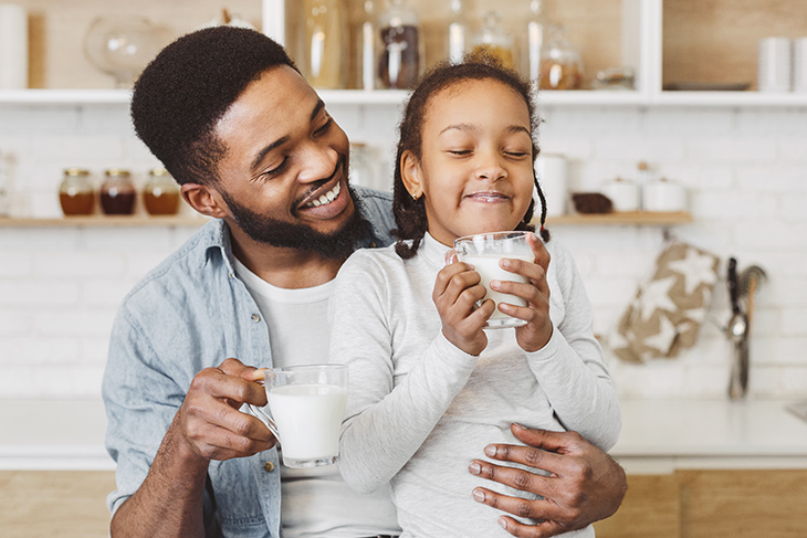 Photo of black man and child drinking milk in a family moment.