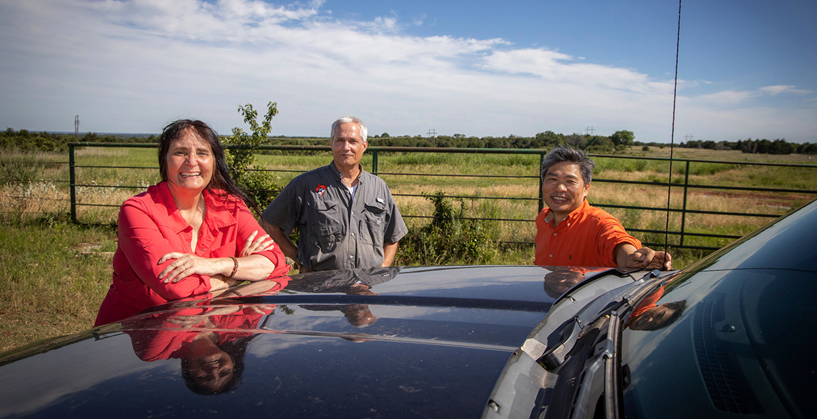 Photo of Gail Wilson, Rodney Will and Chris Zhou out among the grasslands.