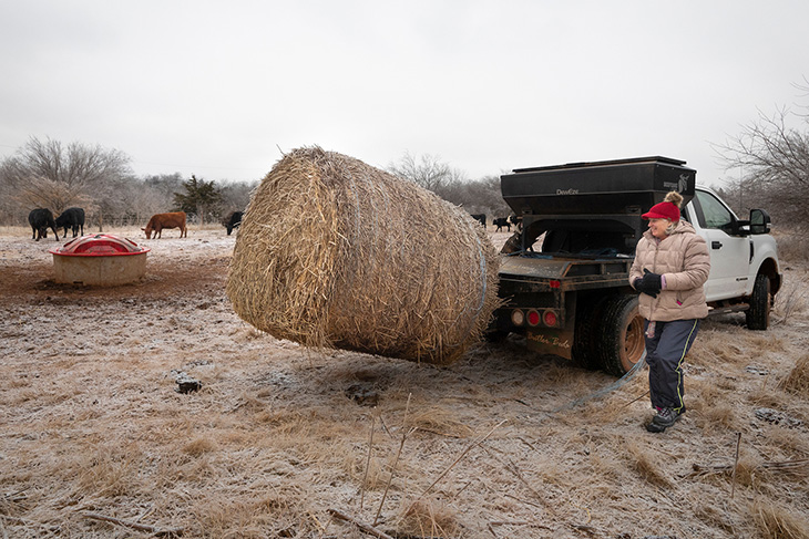 Photo of Marka Acton unloading a hay bale.