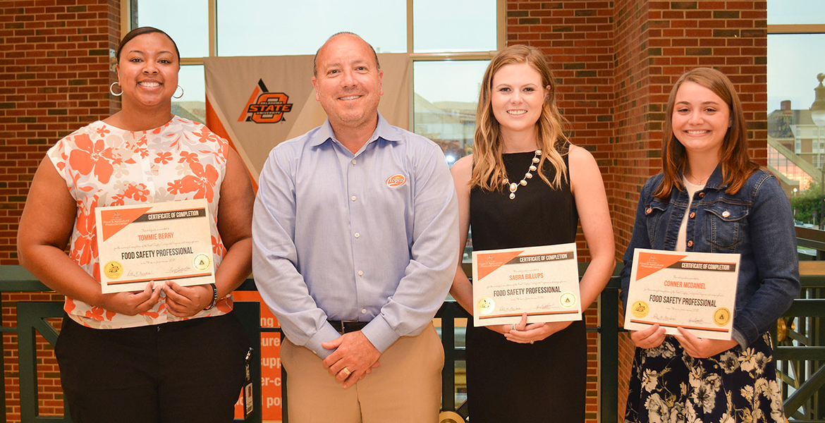 John Lopez of Lopez Foods and chair of FAPC's Industry Advisory Committee presents Tommie Berry of QuickTrip and Sabra Billups and Conner McDaniel, OSU graduate students, with certificates for completing the Food Safety Professional program.