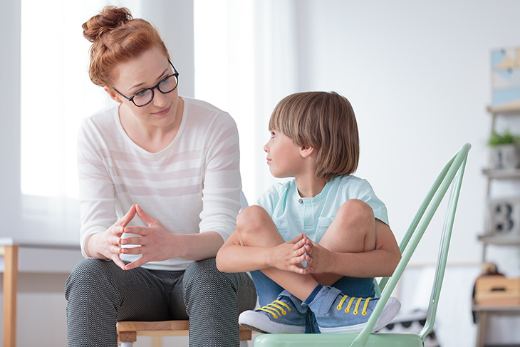 Photo of adult talking with child.