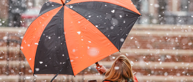 Girl holds Oklahoma State University umbrella in snow storm.