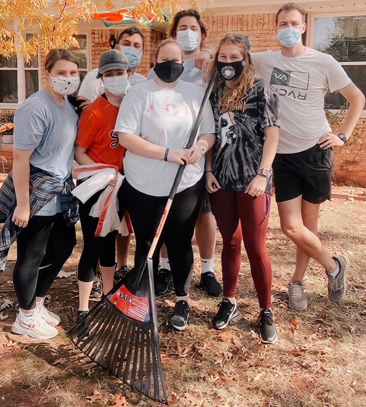 OSU students raking leaves in a resident's yard