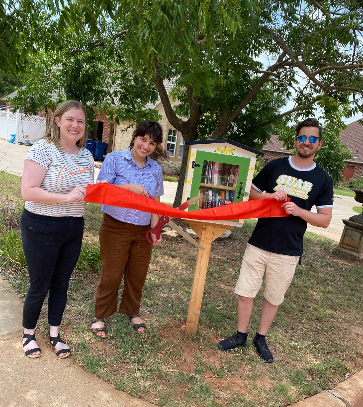People ribbon cutting at a Little Free Library.