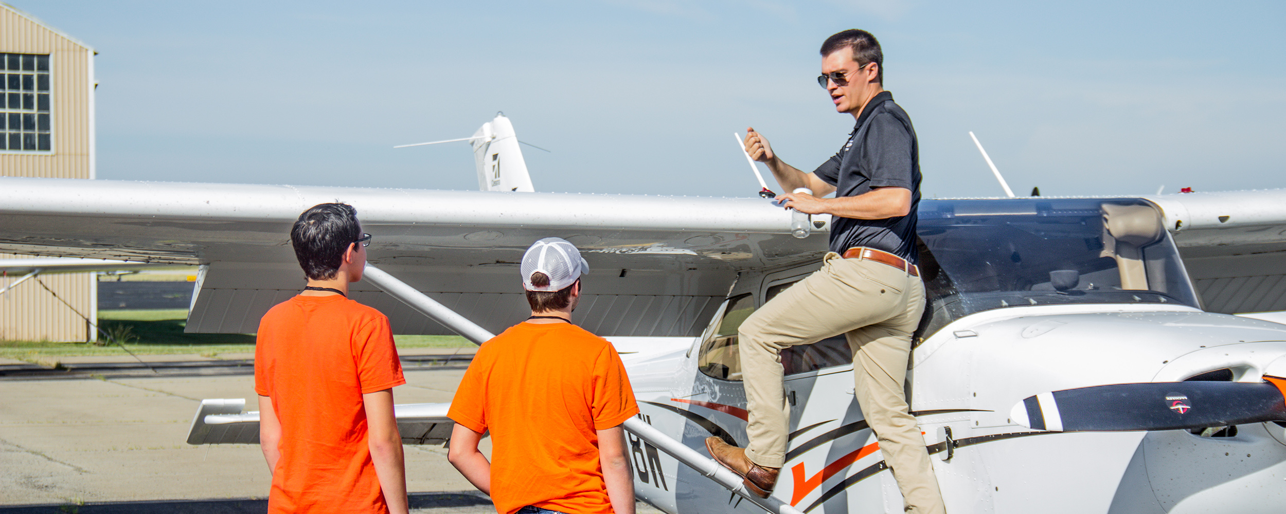 Student pilot on wing of airplane during flight camp