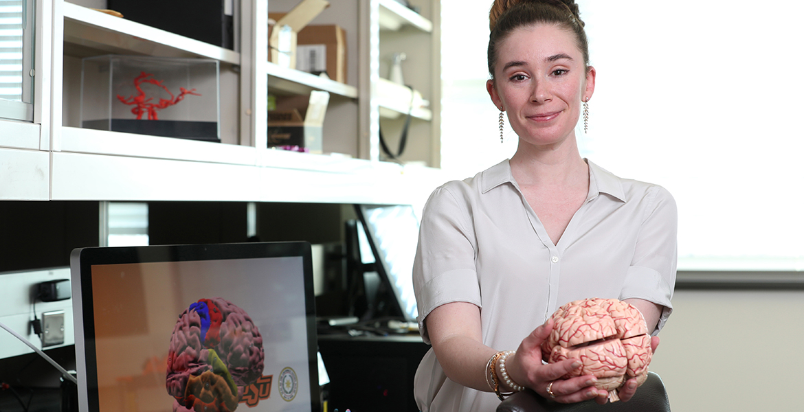 OSU-CHS Assistant Professor of Anatomy and Cell Biology Haley O'Brien, Ph.D., stands in her lab holding the 3D model of a brain.