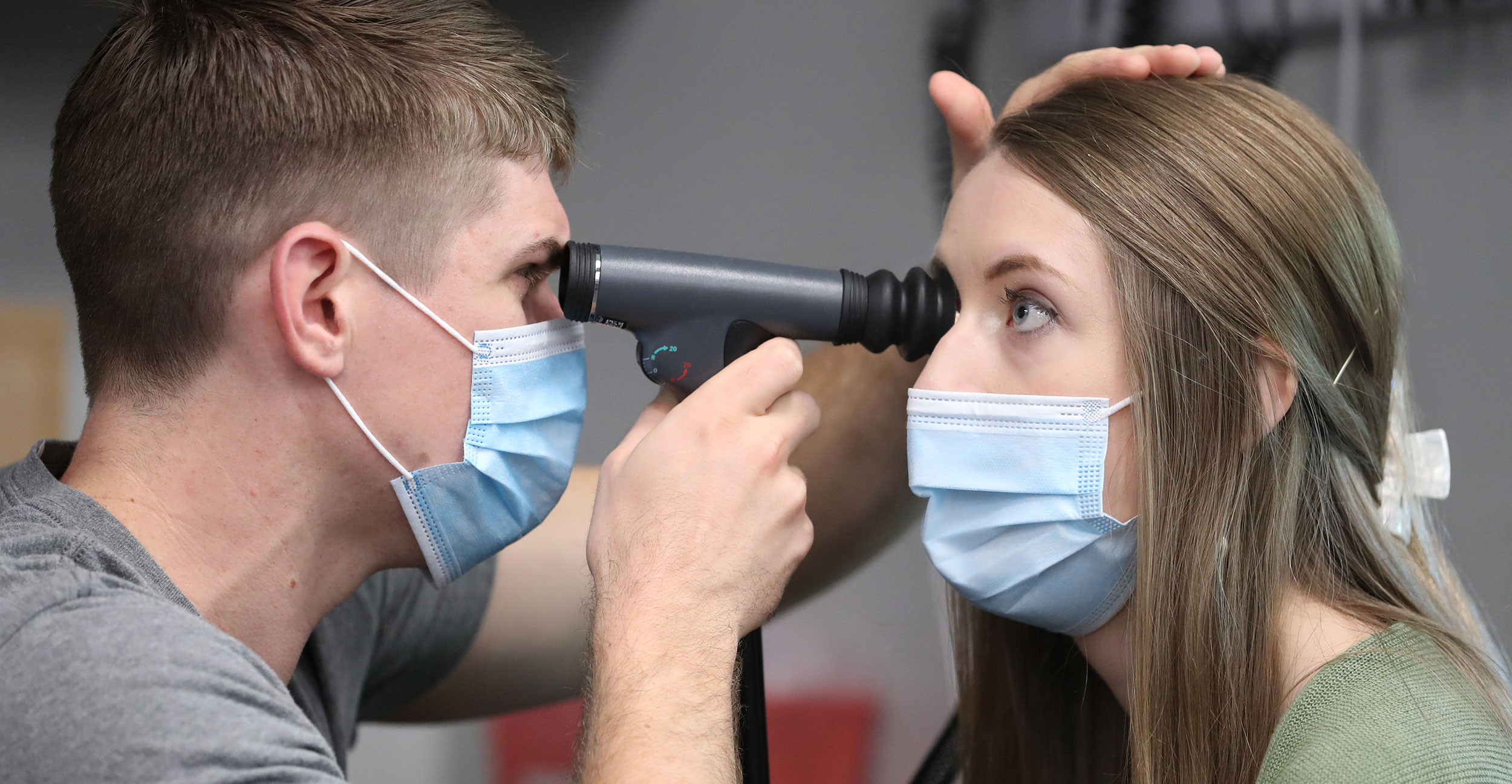 Medical student Cooper Anderson (left) uses an ophthalmoscope on optometry student Baylee Moles (right) from Northeastern State University Oklahoma College of Optometry during an interprofessional education session at OSU College of Osteopathic Medicine at the Cherokee Nation in Tahlequah.
