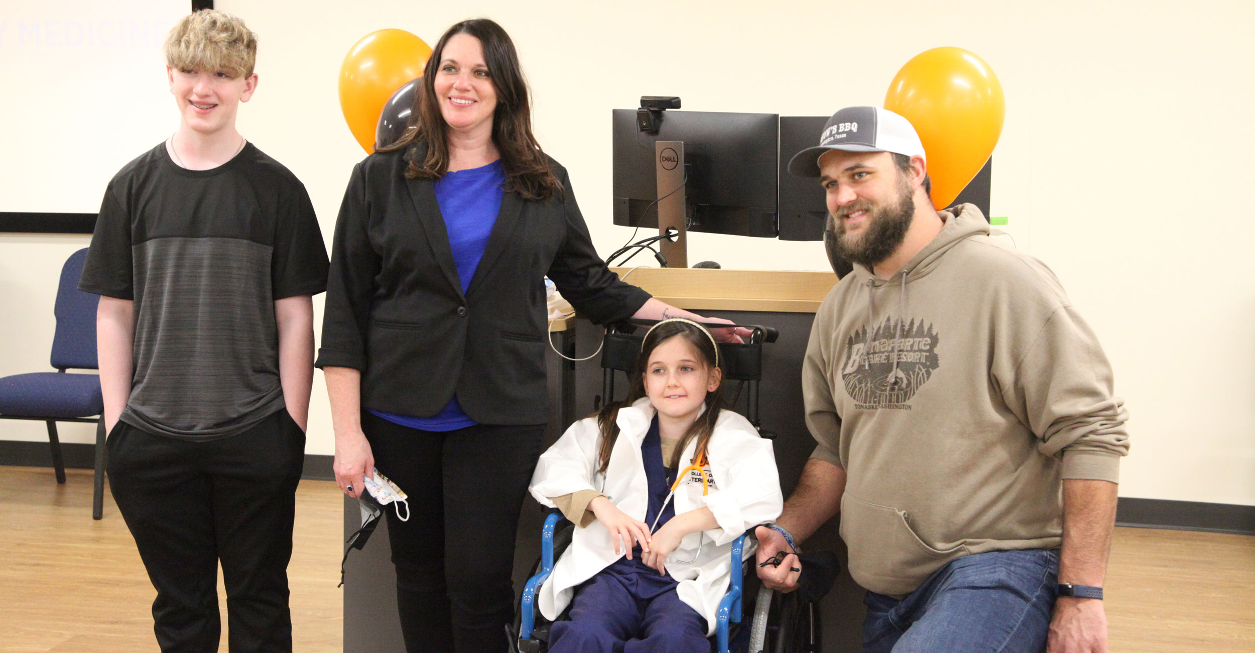 Addie, an 8-year-old cancer patient from Tulsa, visited OSU as part of the Make-A-Wish program. Pictured (left to right): Her brother, Tyler; her mom, Renee; Addie; and her dad, Ben.