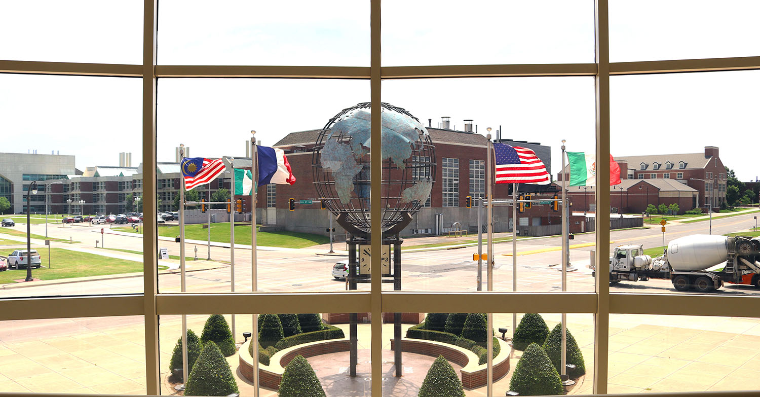 Looking out wes watkins window at globe statue and flags