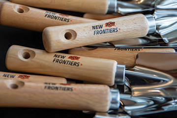 Garden shovels branded with the New Frontiers logo signify the groundbreaking of the New Frontiers Agricultural Hall.