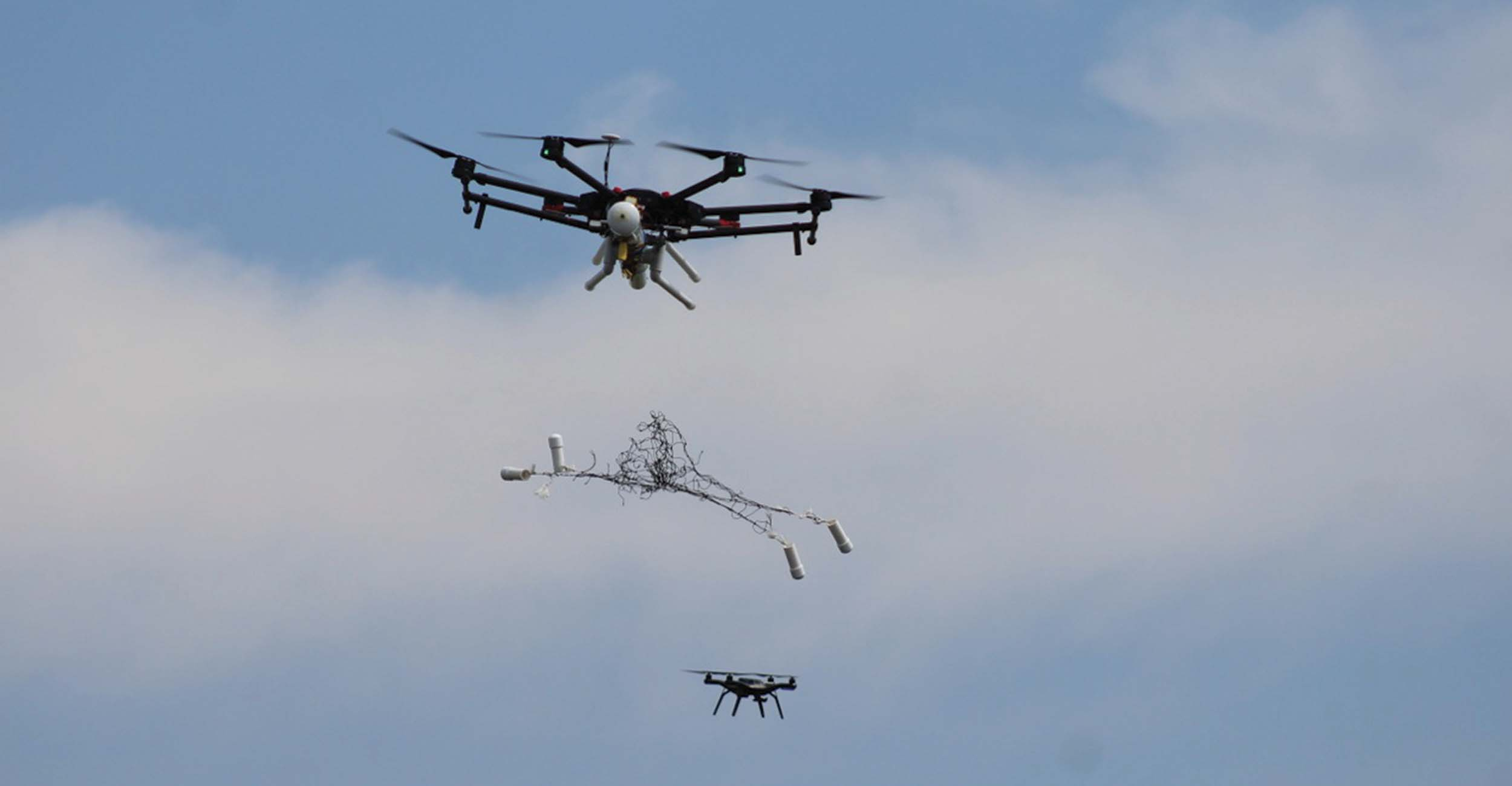 Drone throwing a net at another drone