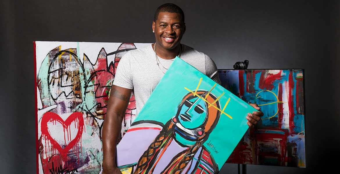 Desmond Mason holding a piece of his art