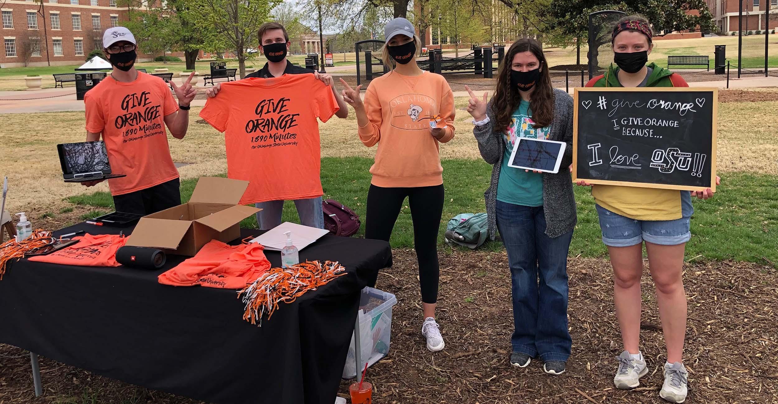 Students hold up Give Orange shirts.