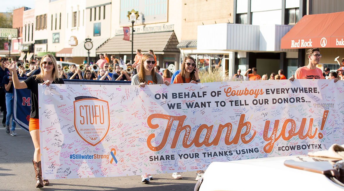 The Student Foundation carrying a Stillwater Strong banner during a parade.