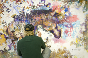 A student paints a work during a studio class.